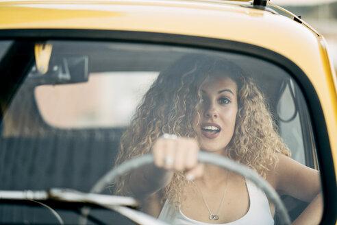 Portrait of surprised blond woman driving classic car - OCMF00028