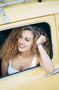 Smiling young woman looking out of car window - OCMF00031