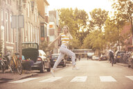 Young woman jumping in the air on zebra crossing - JESF00190