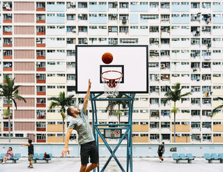 China, Hong Kong, Kowloon, man playing basketball, public housing in the background - GEMF02437