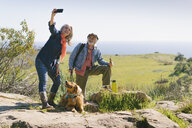 Mature woman taking selfie with man and Golden Retriever while hiking at countryside - TGBF00822
