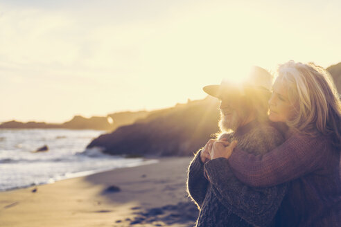 Side view of senior couple embracing  at beach on sunny day - TGBF00858
