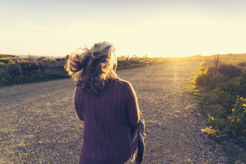 Rear view of mature woman walking on dirt road during sunset - TGBF00861