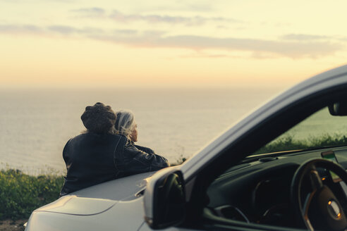 Rear view of couple looking at ocean while leaning on car during sunset - TGBF00873