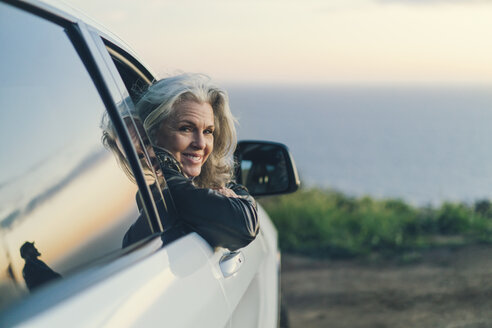 Portrait of mature woman smiling while leaning on car window at countryside - TGBF00879
