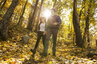 Full length of loving male and female backpackers walking in forest on sunny day during autumn - TGBF00891