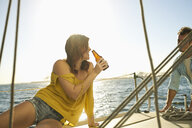 Happy woman holding beer bottle while looking at man on sailboat in sea during summer vacation - TGBF00915