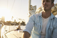 Thoughtful man looking away while sitting on sailboat during summer vacation - TGBF00918