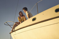 Couple talking while sitting on sailboat against clear sky - TGBF00921