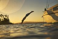 Man diving into ocean from sailboat at sunset - TGBF00924