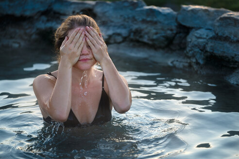 Woman Covering Face While Relaxing In Hot Spring - TGBF00933