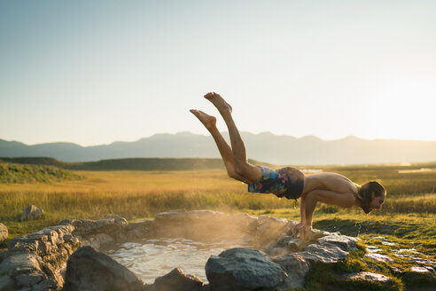 Young Man Performing Handstand Over Hot Spring - TGBF00942
