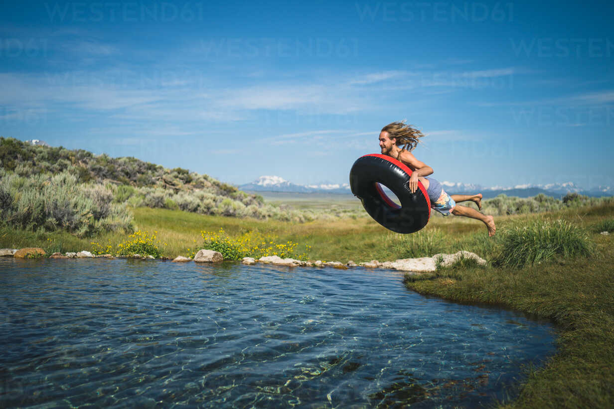 Man With Inflatable Ring Jumping In Lake - TGBF00948 - The Good Brigade/Westend61