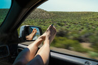 Woman With Legs On Window Enjoying Road Trip In Car - TGBF00963