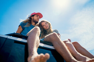 Woman leaning on man while sitting on roof of car during summer - TGBF00966