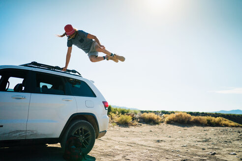 Man Jumping Over Car Against Sky - TGBF00975