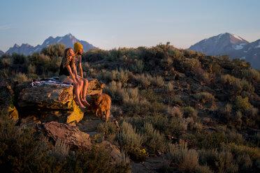 Couple Sitting With Dog On Mountain enjoying sunset - TGBF00984