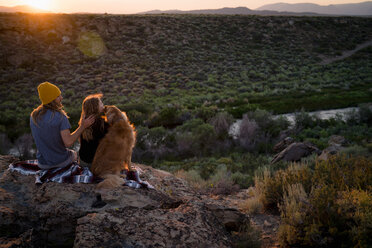 Hikers Sitting With Dog On Rock While Enjoying Nature - TGBF00987