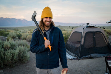 Portrait of male hiker holding axe at campsite - TGBF00990
