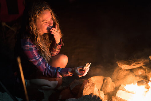 Female Hiker Eating Food By Campfire At Night - TGBF00996