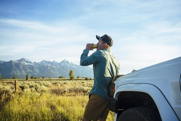 Side view of young man drinking beer while leaning against white truck - TGBF01005