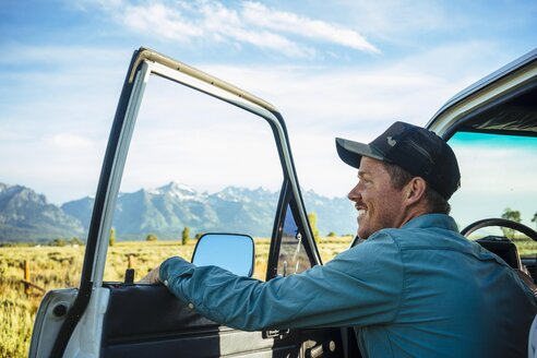 Young male tourist by car sightseeing at Grand Teton National Park - TGBF01008
