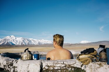 Rear view of young man relaxing in natural  hot spring near Mammoth Lakes - TGBF01011