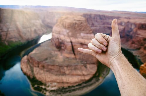 Cropped image of male tourist gesturing against Colorado River at Horseshoe Bend - TGBF01020