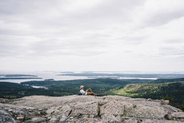 Relaxed male backpacker reading book on mountain at Acadia National Park against sky - TGBF01032