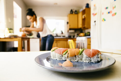 Closeup of sushi on plate with woman cooking in background at kitchen - TGBF01038
