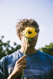 Portrait of young man covering face with sunflower against sky - TGBF01068