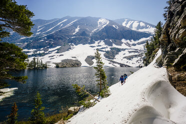 Hikers hiking on snow covered mountain by river at Sequoia National Park - TGBF01074