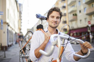 Portrait of content young man carrying his racing cycle on shoulder in the city - PNEF01083