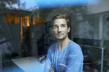 Portrait of young man in an office looking out of window - PNEF01107