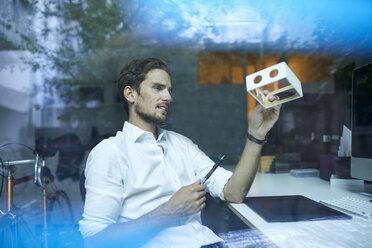 Serious young man behind windowpane examining prototype - PNEF01113