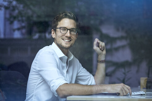 Portrait of smiling young man behind windowpane sitting at his office desk - PNEF01116