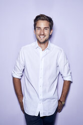 Portrait of smiling young businessman in front of purple background - PNEF01122