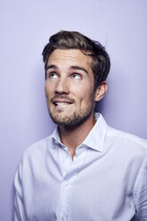 Portrait of young man in front of purple background raising eyebrows - PNEF01125