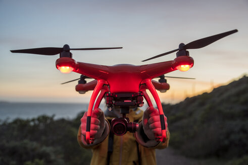 Boy holding illuminated drone while standing against sky during sunset - CAVF52365