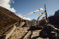 Colorful prayer flags hanging on mountain against blue sky during sunny day - CAVF52377