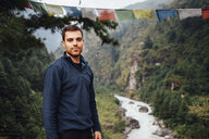 Portrait of hiker standing against river amidst mountains at Sagarmatha National Park - CAVF52386