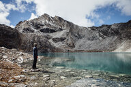 Side view of man standing at lakeshore against cloudy sky at Sagarmatha National Park - CAVF52392