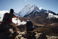 Friends with backpacks sitting on mountain against blue sky at Sagarmatha National Park - CAVF52404