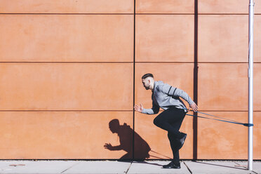 Side view of man exercising with resistance band by wall on sidewalk - CAVF52416