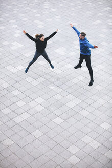 High angle view of couple with arms outstretched jumping on sidewalk - CAVF52422