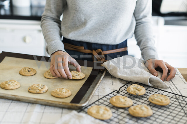 Midsection of woman arranging cookies on cooling rack in kitchen - CAVF52425