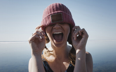 Woman wearing knit hat screaming against sea during sunny day - CAVF52446