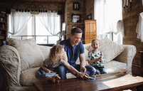 Happy father playing with children while sitting on sofa in living room - CAVF52452