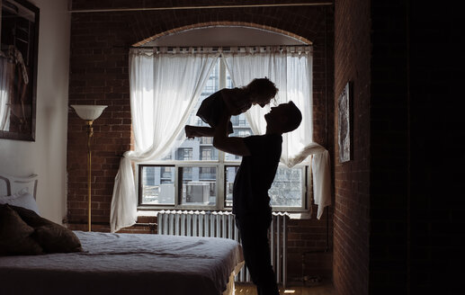 Silhouette father picking up daughter while standing by bed at home - CAVF52458