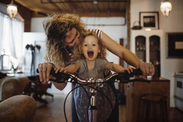 Mother with daughter riding bicycle at home - CAVF52461